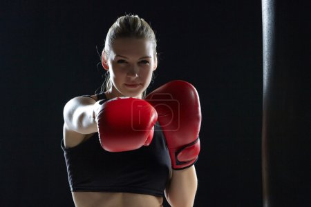 Photo for Beautiful woman with the red gloves is boxing on black background - Royalty Free Image