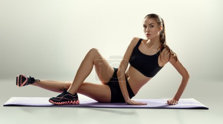 Photo for Attractive woman do fitness exercise on a lilac mat on grey background - Royalty Free Image