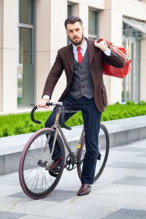 Photo for Handsome businessman in a jacket with red bag sitting on  his bicycle on city streets. The concept of the modern lifestyle of young men - Royalty Free Image