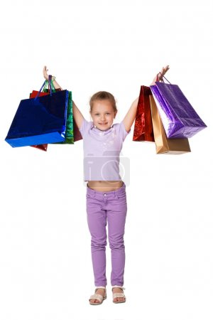 Photo pour Fille heureuse avec des sacs à provisions debout au studio, isolé sur fond blanc - image libre de droit