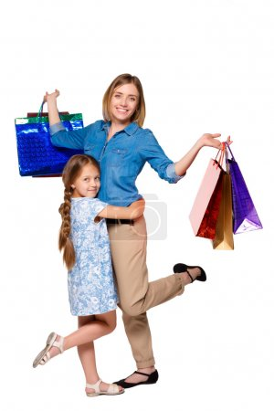 Photo for Happy  mother and daughter with shopping bags standing at studio, isolated on white background.  daughter hugging her mother - Royalty Free Image