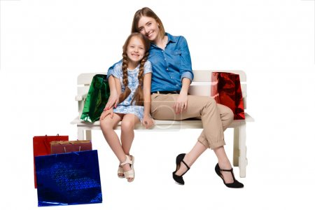 Photo for Happy  mother and daughter with shopping bags sitting at studio, isolated on white background - Royalty Free Image