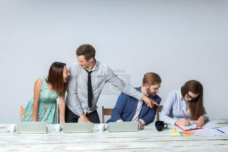 Photo pour Équipe d'affaires travaillant sur leur projet d'affaires ensemble au bureau sur le fond gris clair. tout souriant et regardant le patron. le patron écrit dans un carnet. image copyspace - image libre de droit