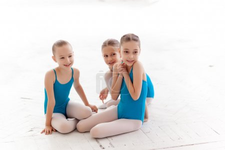 Three little ballet girls sitting and talking together