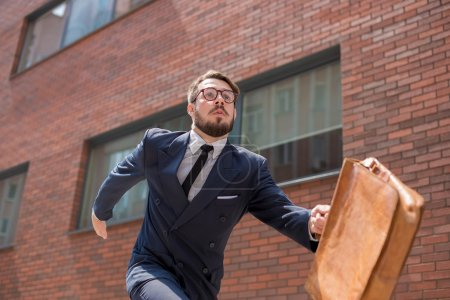 Photo for Young businessman with a briefcase and glasses running in a city street on a background of red brick wall - Royalty Free Image
