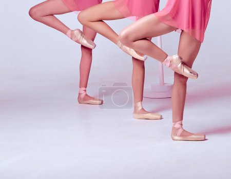 Photo for Three young ballerinas stretching on the bar on beige background - Royalty Free Image