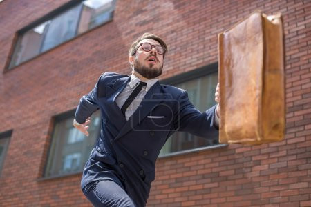 Photo for Young businessman with a briefcase and glasses running in a city street on a background of red brick wall. concept of rapid career - Royalty Free Image