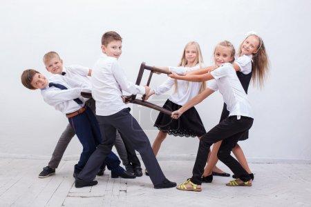 Kids playing tug of chair - girls versus boys,