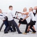 Kids playing tug of chair - girls versus boys on w...