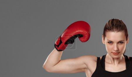 Photo pour Belle gagnante. Belle femme aux cheveux blonds en gants de boxe rouges debout sur fond gris - image libre de droit
