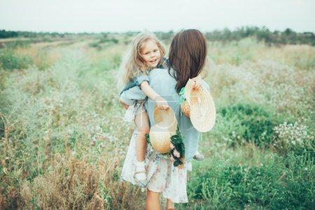 Photo pour La jeune mère et sa fille avec des chapeaux sur fond d'herbe verte - image libre de droit
