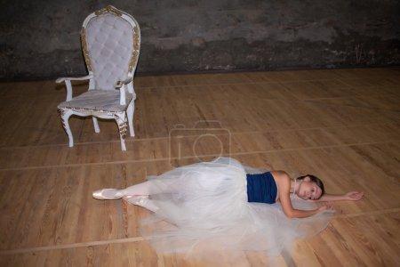 Photo pour La belle ballerine couchée dans une longue jupe blanche sur fond de sol en bois - image libre de droit