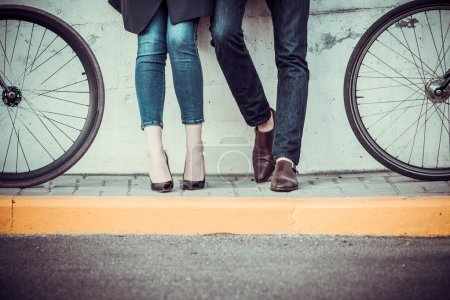 Photo pour Les jambes d'un jeune couple assis sur des vélos en face de la ville - image libre de droit