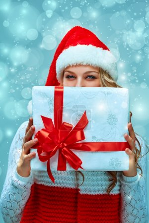 Photo for Girl dressed in santa hat  with a Christmas gift. She looking at camera. Holiday concept with blue background - Royalty Free Image