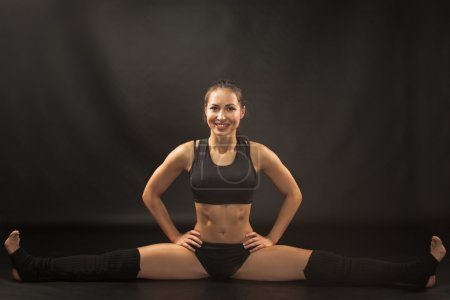 Muscular young woman athlete sitting in the split on black