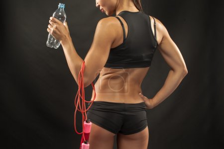 Photo for The back of muscular young woman athlete  with a skipping rope drinking water on black background - Royalty Free Image