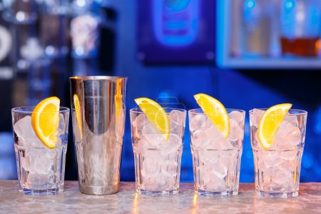 Photo for Glasses with ice cubes and lemons on the  bar and shaker - Royalty Free Image