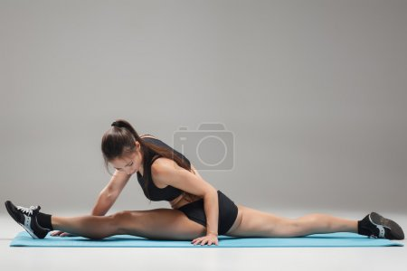 Muscular young woman athlete sitting in the split on gray