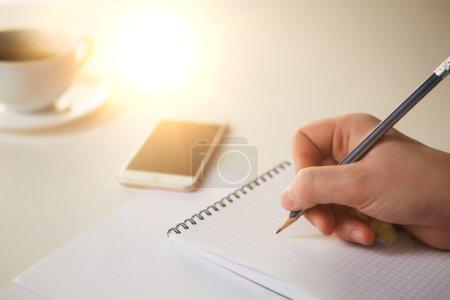 Photo pour Les mains masculines avec un crayon et la tasse de café et carnet sur la table - image libre de droit