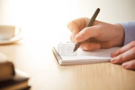 Photo pour La main mâle avec un stylo et la tasse de café et portable - image libre de droit