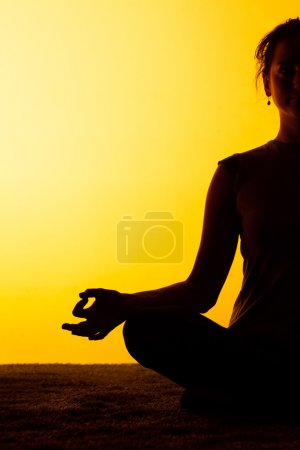 The woman practicing yoga in the sunset light