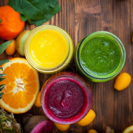 Blended green,yellow and purple smoothie with ingredients select