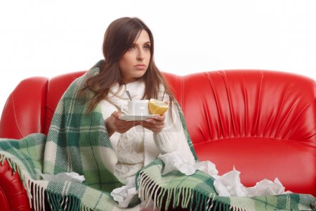 Photo for Sick young woman sitting on a red sofa and drinking tea with lemon. Young female caught cold, feeling bad, wrapped up in blanket, squeezing lemon to her tea - Royalty Free Image