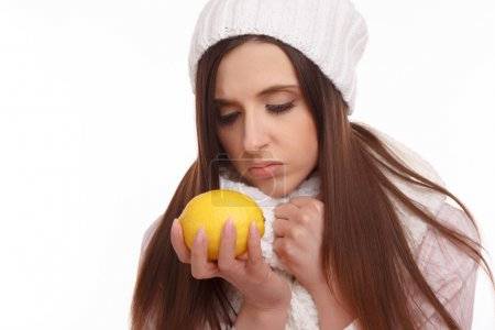 Photo for Sick young woman in pajamas and scarf holding lemon on white background - Royalty Free Image