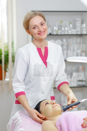 Young woman beautician is doing the cleaning procedure