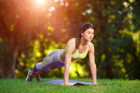 Photo for Young smiling woman doing fitness exercises in the park on the green grass. Fitness training in the sunlight. - Royalty Free Image