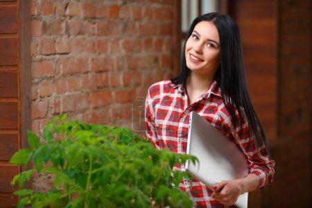 Photo pour Une vie verte. Tourné d'une jolie jardinière debout avec un ordinateur portable regardant la caméra posant joyeusement dans sa serre personnelle . - image libre de droit