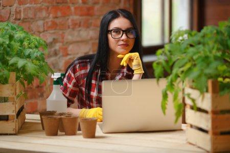 Photo pour Rester connecté. Portrait d'un jeune beau jardinier assis à l'aide d'un ordinateur portable regardant vers la caméra souriant . - image libre de droit