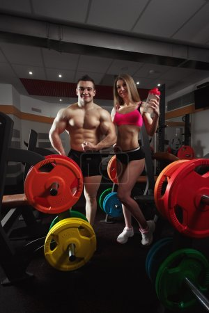 Fitness couple in the gym. Athletic couple poses f...