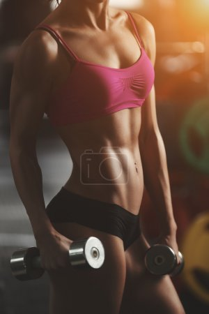 Photo for Brutal athletic woman pumping up muscles with dumbbells. Brunette sexy fitness girl in pink sport wear with perfect body in the gym posing before training set. Attractive fitness woman - Royalty Free Image