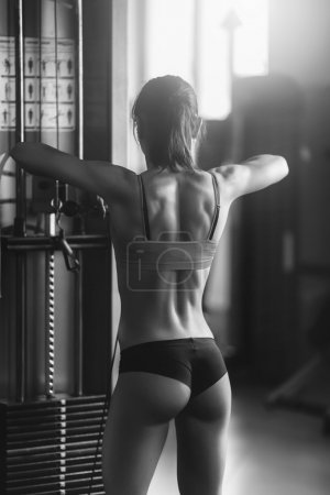 Photo pour Black and white photo of a strong woman. Brunette sexy fitness girl in sport wear with perfect body in the gym posing before training set - image libre de droit