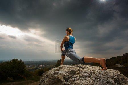 Photo pour Femme faisant du yoga contre le soleil couchant. Cours de fitness en plein air. Ciel orageux avec soleil - image libre de droit