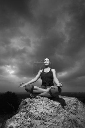 Photo pour Photo en noir et blanc d'une femme faisant du yoga contre le soleil couchant. Cours de fitness en plein air. Ciel orageux avec soleil - image libre de droit