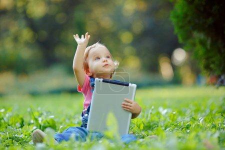 Photo pour Enfant jouant avec tablette à l'extérieur. Enfant joyeux avec un PC portable dans vos mains. Le gamin regarde ailleurs - image libre de droit