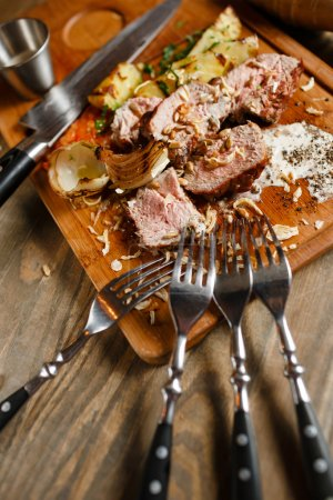Photo for Meat dish natural appearance. Appetizing slices of meat, sliced on a wooden board with a side dish of baked potato and onion slices, sprinkle with spices, black pepper, seeds and garlic - Royalty Free Image