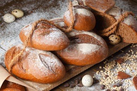 Photo pour Variété de pain de seigle sur fond de bois avec farine, grains et oeufs de caille - image libre de droit