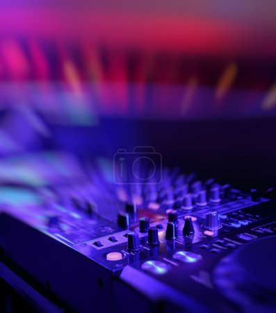 DJ mixer with light colored spotlights discos