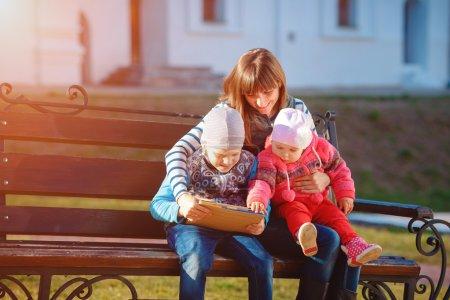 Photo pour Famille heureuse de trois, mère, fils et fille s'asseyant sur un banc dans l'après-midi dans le parc de ville et tiennent une tablette, un beau temps de printemps, le soleil brille - image libre de droit