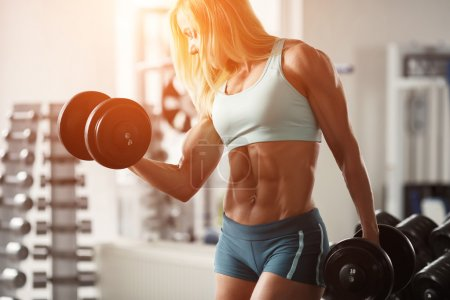 Photo for Strong woman bodybuilder with white hair and tanned body pumps up the muscles lifting dumbbells in the gym. Horizontal frame with space for text - Royalty Free Image