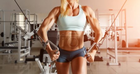Photo for A strong blond woman with muscular and tanned body doing exercise on the chest in the crossover in the gym, not a standard view, a wide viewing angle. - Royalty Free Image