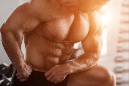 Photo for Brutal man bodybuilder shows muscles of the chest, abdomen and arms. Strong man flexing his muscles. Part of the body close-up - Royalty Free Image