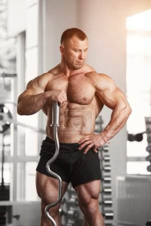 Strong man holding a curved barbell