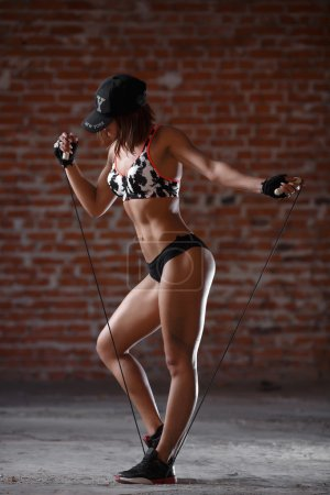 Photo for Beautiful fitness woman with the jump rope on the brick wall background. Healthy lifestyle, diet and fitness - Royalty Free Image