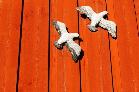 Sculpture white gulls attached to the deep red wal...