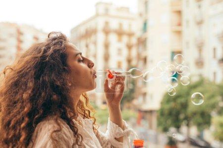 Photo pour Fille jouant avec des bulles d'air. Jeune femme joue souffle un jouet de bulle d'air comme un petit enfant, s'amusant par une journée ensoleillée à l'extérieur . - image libre de droit