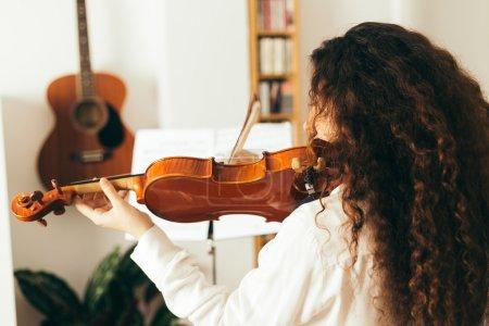 Photo pour Une fille qui joue du violon. Jeune femme étudiant la musique seule à la maison dans le salon avec lumière naturelle et douce . - image libre de droit